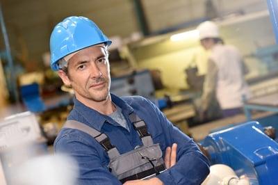 Portrait of mature metal worker standing in workshop